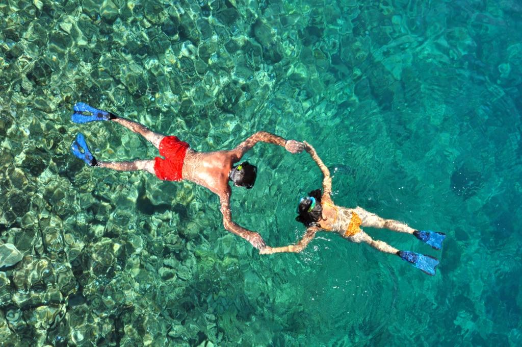 pareja haciendo snorkeling cogidos de la mano