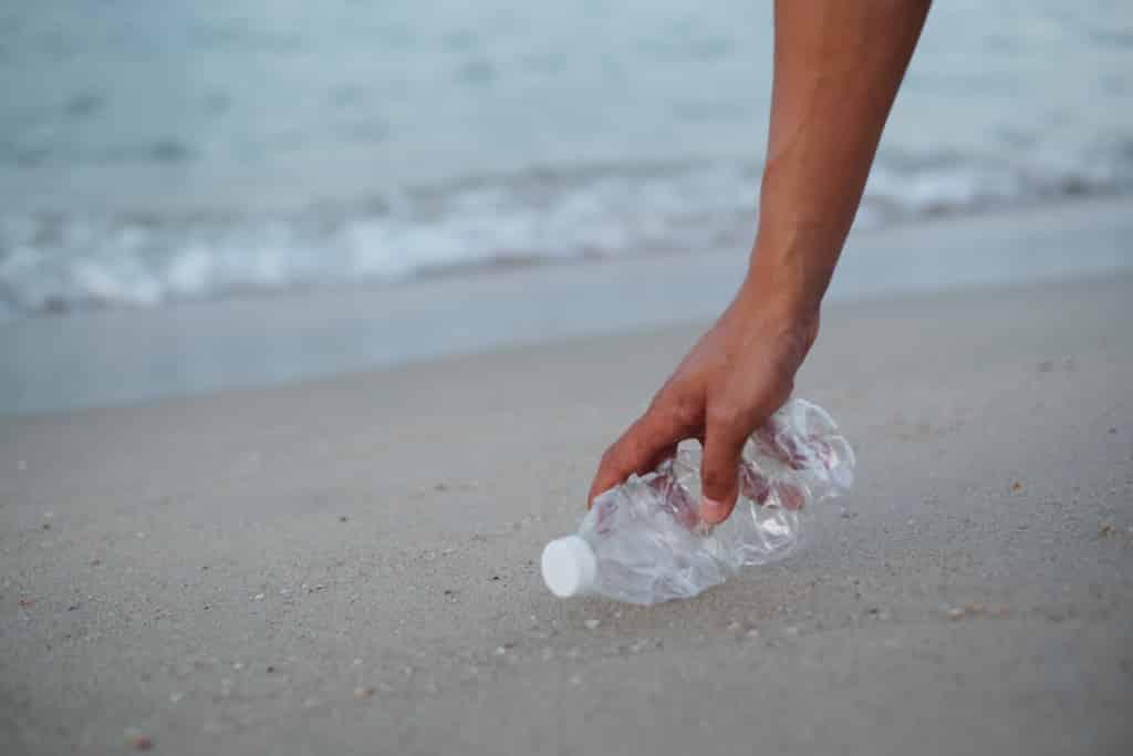mano recogiendo una botella de plástico del suelo de la playa